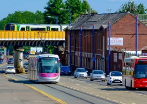 Image shows cars, buses, the tram on a road, with a train running across a bridge behind them